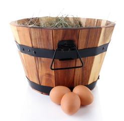 Wooden basket, dried grass and eggs isolated on white