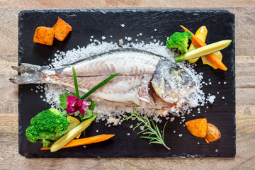 Cooked fish with vegetables in salt