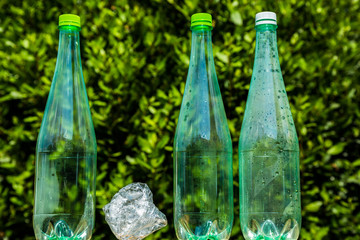 Three plastic bottles with one bottle crushed