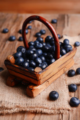 Delicious blueberries in wooden basket on table close-up