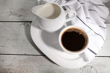 Cup of coffee, creamer on color wooden background