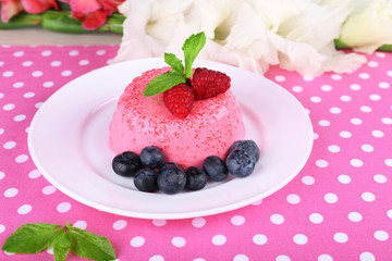 Round shaped cake with berries on plate on polka dot table