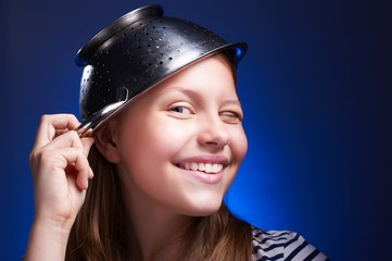 Girl with a colander on her head winking and smiling