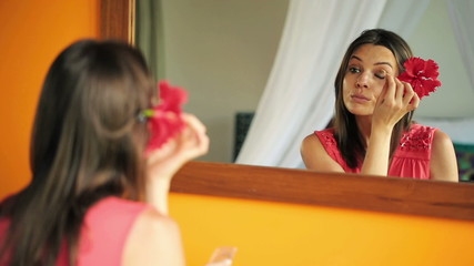 Woman applying makeup, eyeshadow in front of the mirror