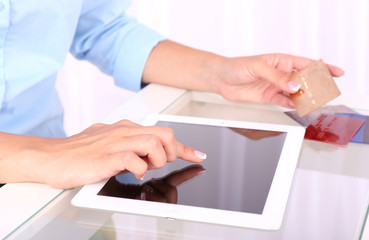 Woman using digital tablet and holding credit card in her hand,