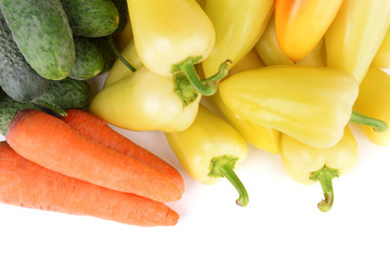 Yellow peppers with cucumbers and carrots close up