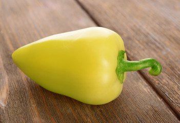 Yellow pepper on wooden background