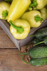 Yellow peppers in crate with cucumbers on wooden background