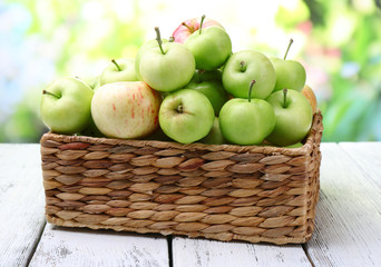 Ripe apples in basket on table on natural background