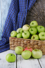 Ripe apples in basket on table close-up
