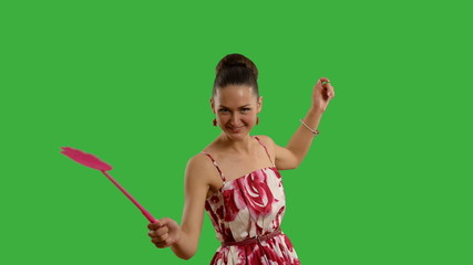 young beautiful woman with swatter smiling on a green screen .