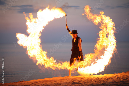 Leinwanddruck Bild Awesome fire show on the beach; circle of flame