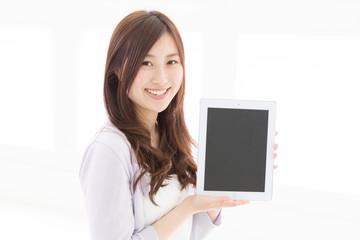 タブレットの画面を見せる女性