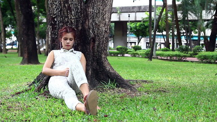 Young woman sitting in the park and play phone