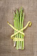 bunch of green asparagus with tape measure