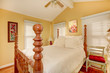 Carved wood high pole bed in bright room