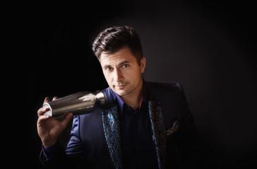 barman holding shaker on black background