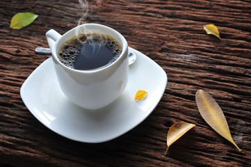 A cup of coffee on wooden table with fallen leaves