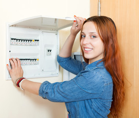 Long-haired smiling woman turning off the light-switch at power
