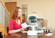 Red haired woman with electric crock pot in her kitchen at home