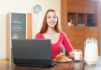 Pssitive happy woman in red using laptop during breakfast at hom