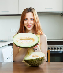 girl with ripe melon at  kitchen