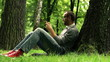 Young man texting, using smartphone in the park