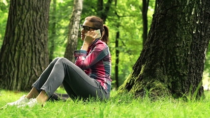 Young woman talking on cellphone in the park
