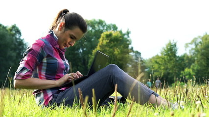 Young woman working on modern laptop in the park