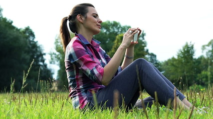 Young woman taking photo with smartphone in the park