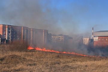 Fire burns grass field brick houses