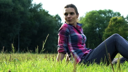 Young woman chilling out on grass in the park