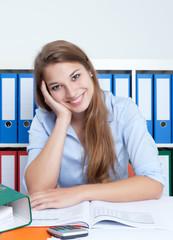 Studentin am Schreibtisch macht Pause