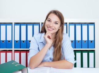 Studentin am Schreibtisch lacht in die Kamera