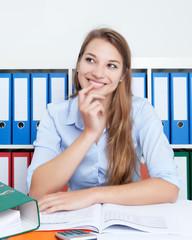 Studentin am Schreibtisch denkt nach