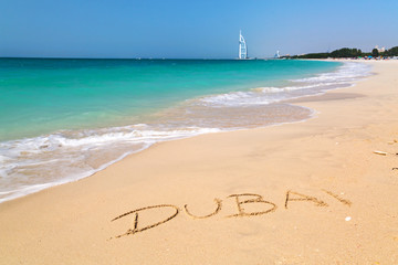 Dubai sign on the beach with turquoise water