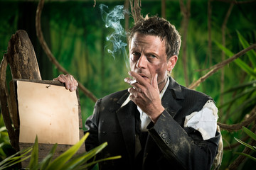 Businessman smoking in the jungle