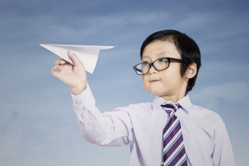 Business kid holding paper airplane outdoor