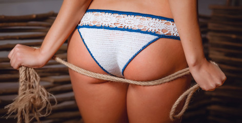 Close-up photo of a girl's backside in a knitted bikini