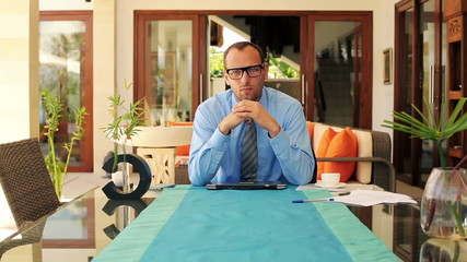 Portrait of young serious businessman sitting by table at home