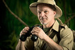 Adventurer in the jungle with binoculars