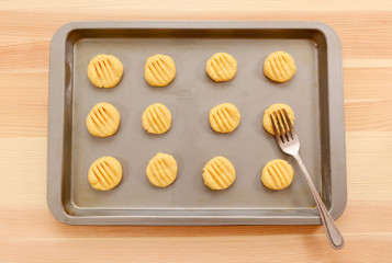 Flattening balls of biscuit dough on a tray