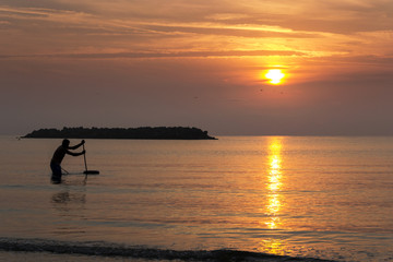 Fishing man in the sea during the sunrise