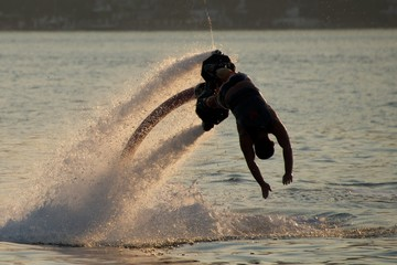 Flyboarder in silhouette diving into evening sea