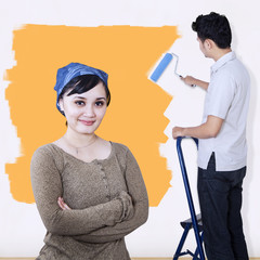 Asian couple painting wall in yellow