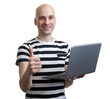Happy young man in t-shirt working on laptop