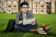 Male student using digital tablet outdoors 1