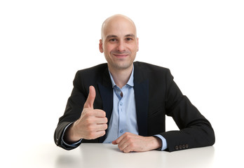 businessman at the table showing thumbs up sign