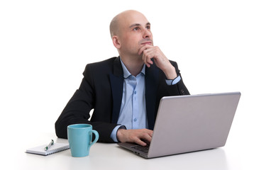 businessman looking up while working at laptop