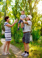 Father, mother and son are playing in nature. Happy family.